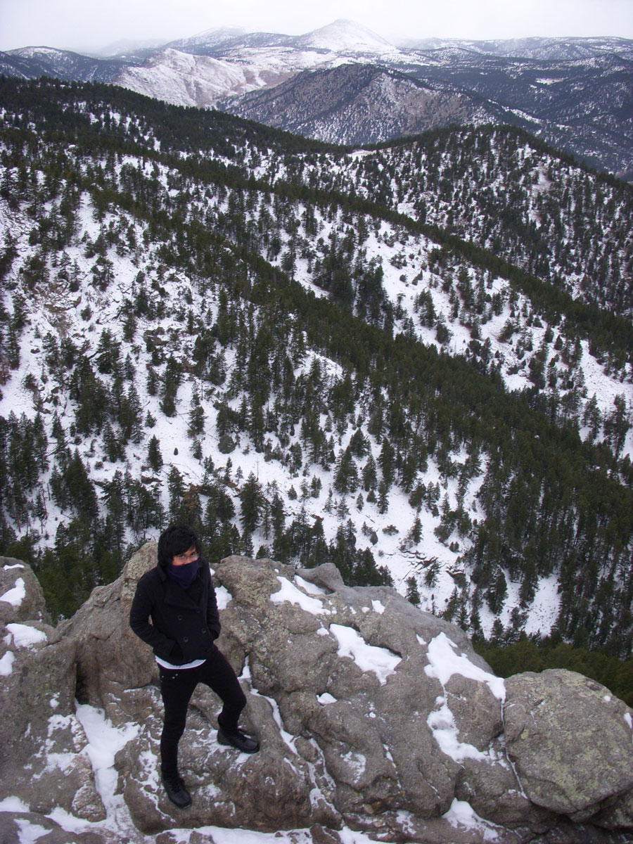 Kevin Banogon stands on top of a mountain.