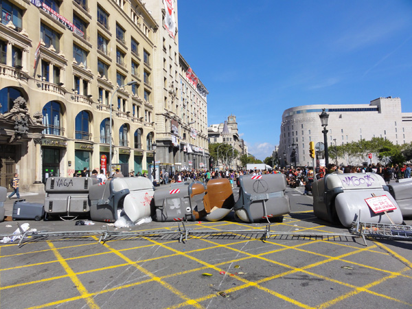 In a riot in Barcelona, trash cans are dragged into the streets.