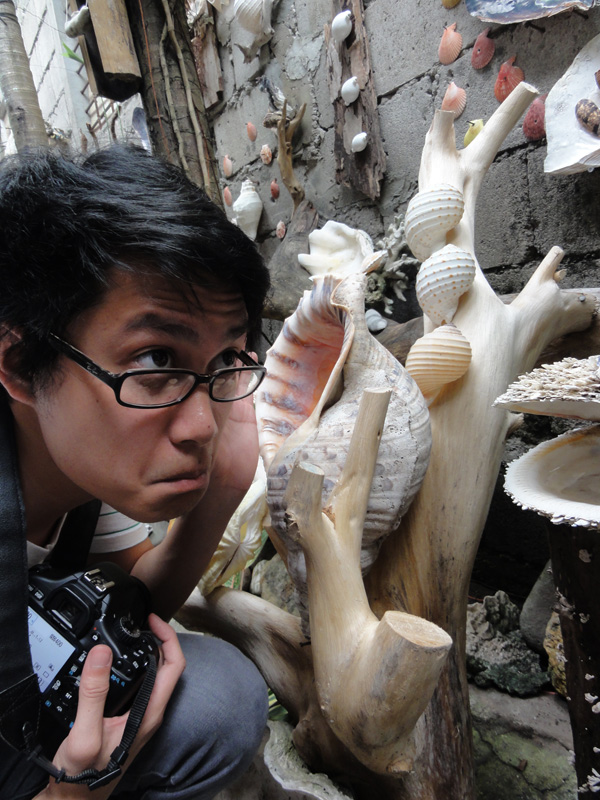Kevin Banogon listens in to a large shell at Shell Garden outside of Dumaguete City.