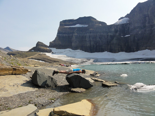 Kevin Banogon and Alicia Doroteo plank on the rocks at Grinnell Glacier.