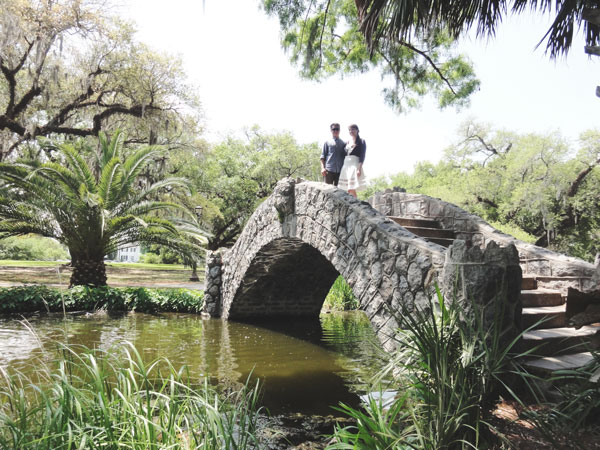 Miami travel bloggers, Meredith Lambert and Kevin Banogon, pose on the stone bridge in City Park in New Orleans.
