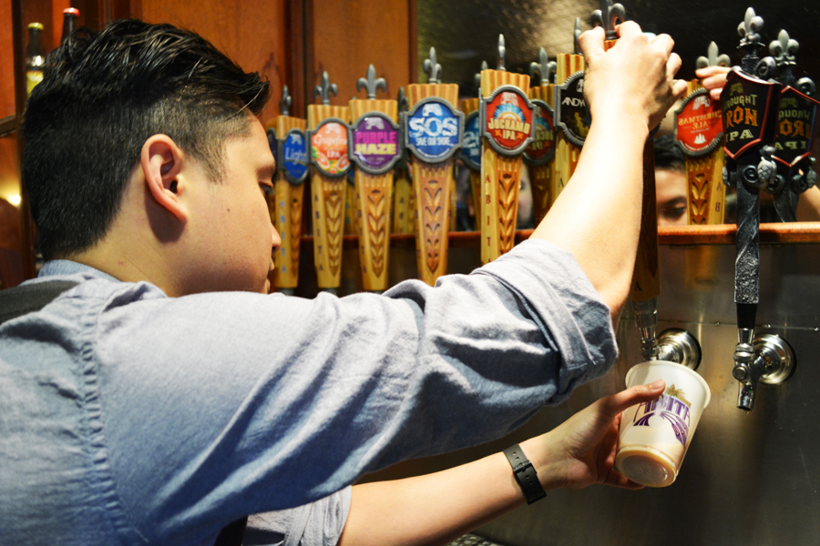 Kevin Banogon learns to pour beer from a tap at the Abita Brewery Tour.