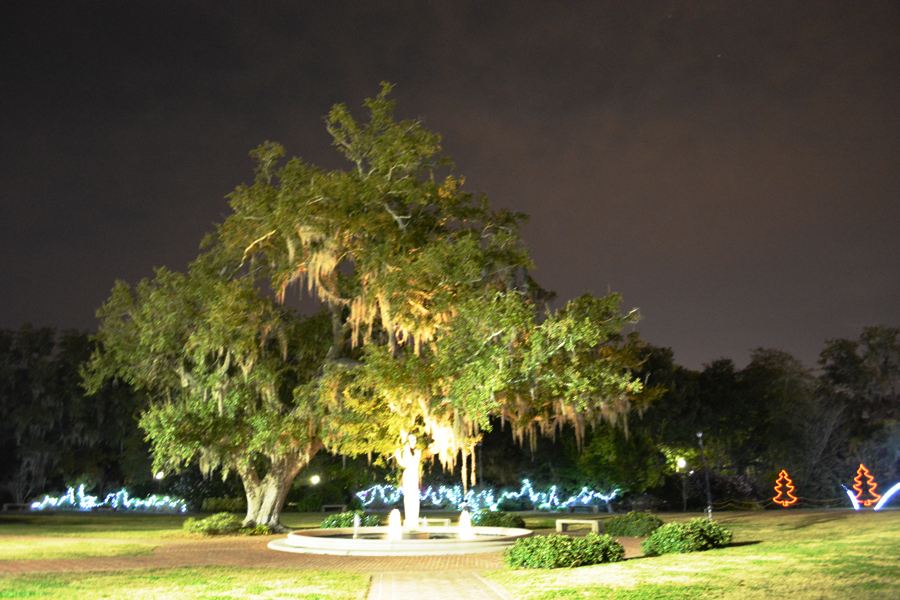A lone statue stands under an oak tree in City Park.