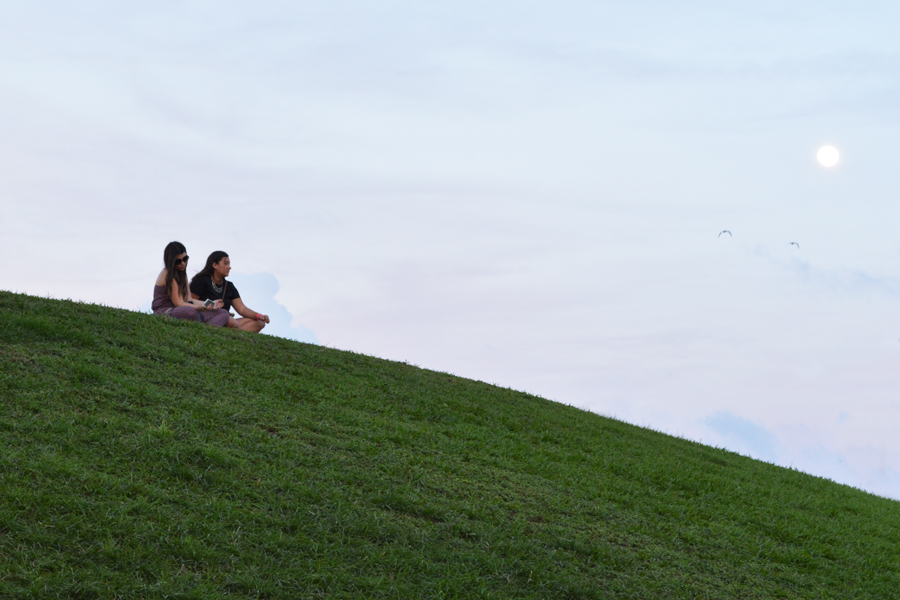 Two girls sit on top the large hill at sunset at South Pointe Park.