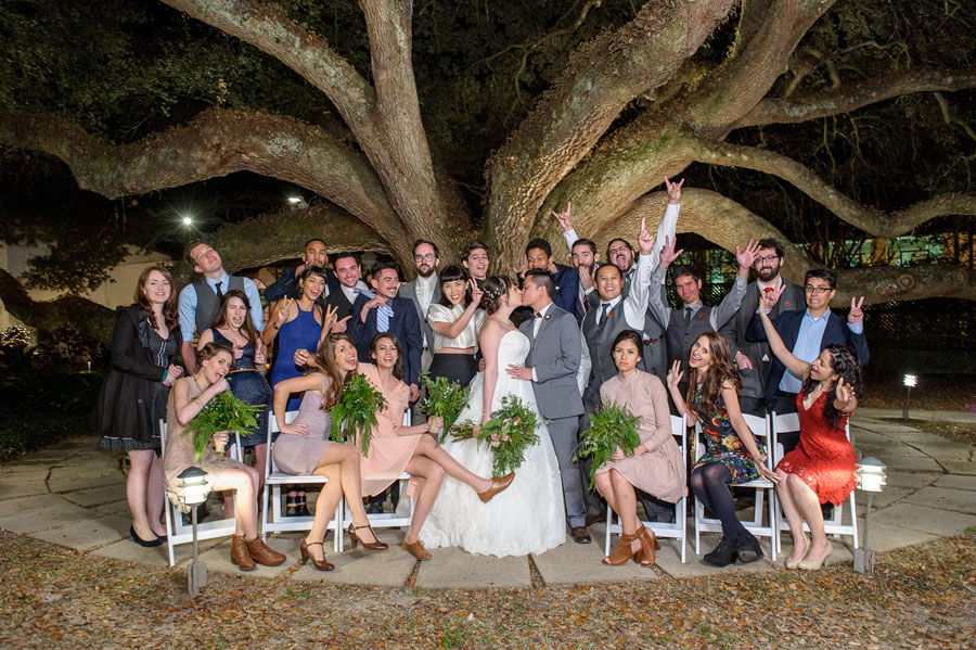 The couple takes a wedding photo with their close friends to celebrate officially being married.
