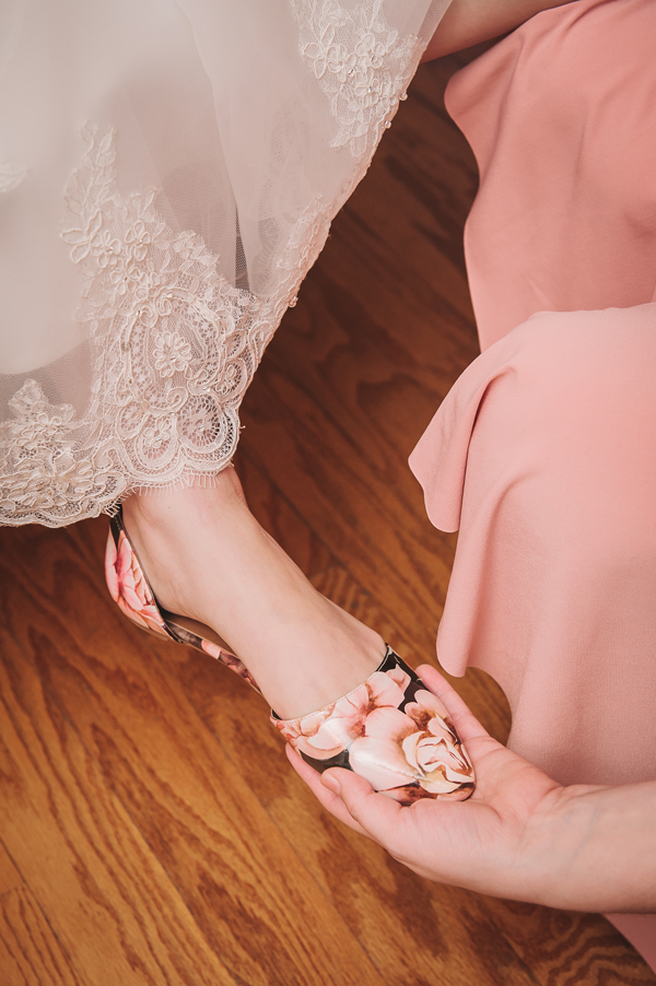 The sister of the bride helps the bride get her shoes on in this wedding photography detail.