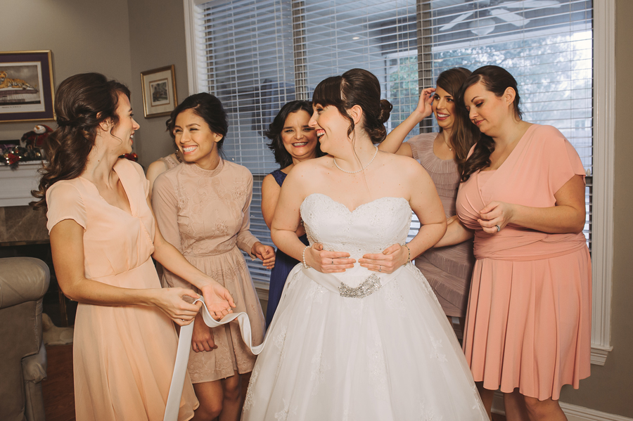 The Covington wedding photographer captures a happy moment between the glowing bride and her bridesmaids.