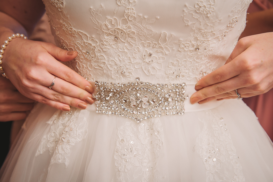 A detailed shot by the wedding photographer of the front of the wedding dress.