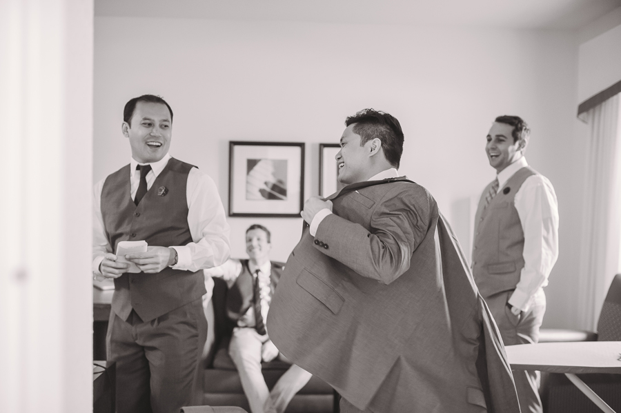 The groom gets ready with his groomsmen while the wedding photographer captures the moment.