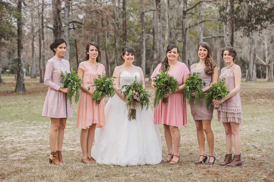 The bride and bridesmaids take formal photos inBogue Falaya Park in Covington, Louisiana.