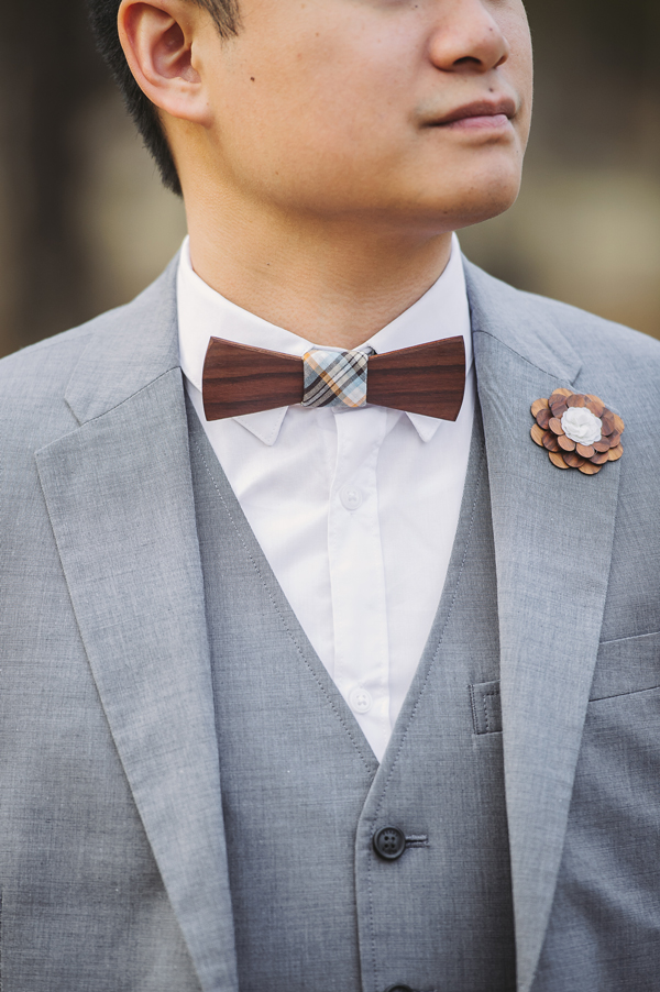 A detail shot of the groom and his wooden bowtie and boutonniere captured by the Covington wedding photographer.