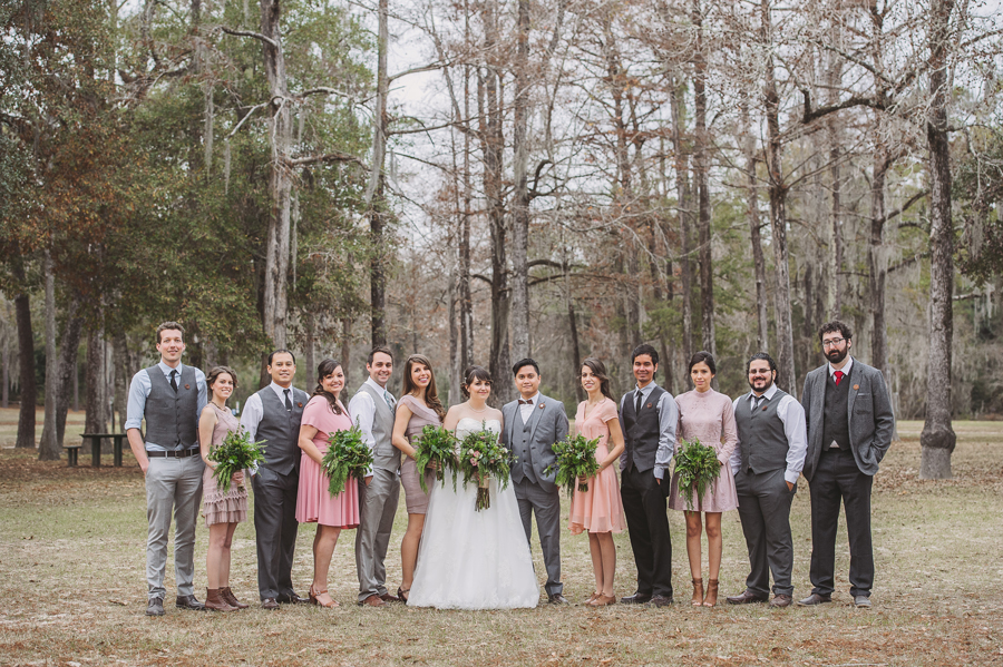 The full bridal party poses for formals with the wedding photography in the Bogue Falaya Park in Covington, Louisiana.