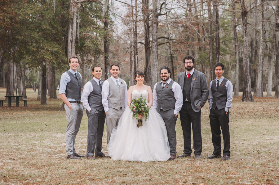 The bride poses with the groomsmen in the wedding formals taken at the Bogue Falaya Park in Covington.