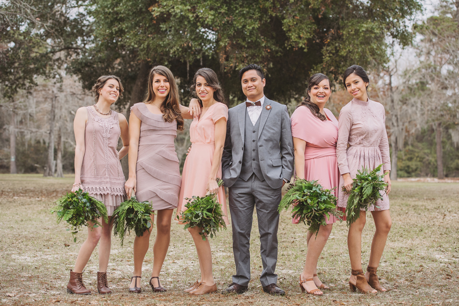 The groom poses with the bridesmaids as the wedding photographer captures formals in the Bogue Falaya Park in Covington.
