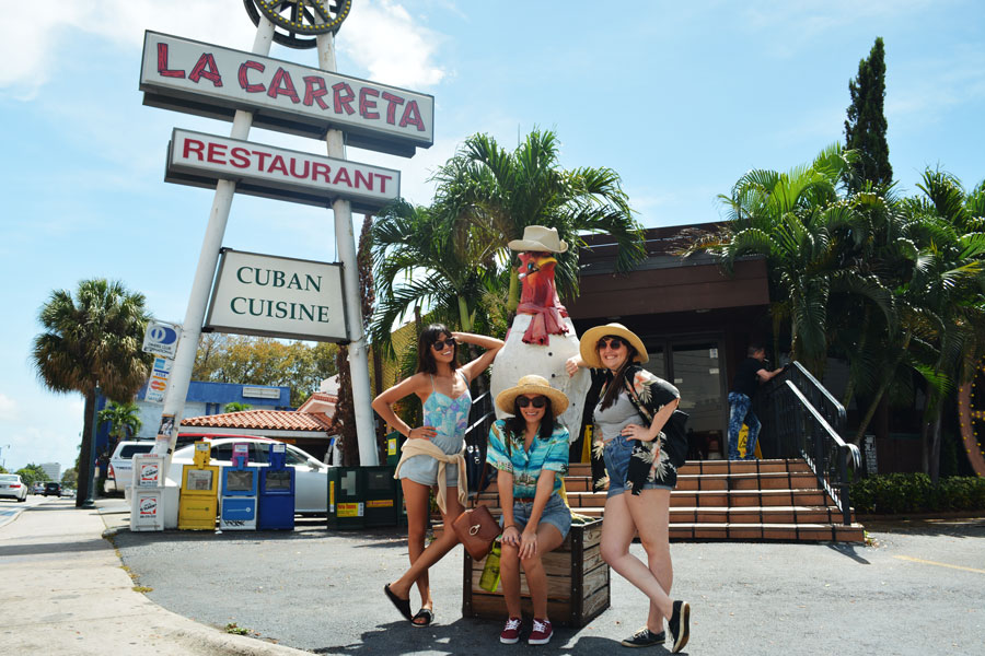Meredith Lambert Banogon, Alicia Doroteo, and Jessica Estrada pose with one of the roosters of Calle Ocho.