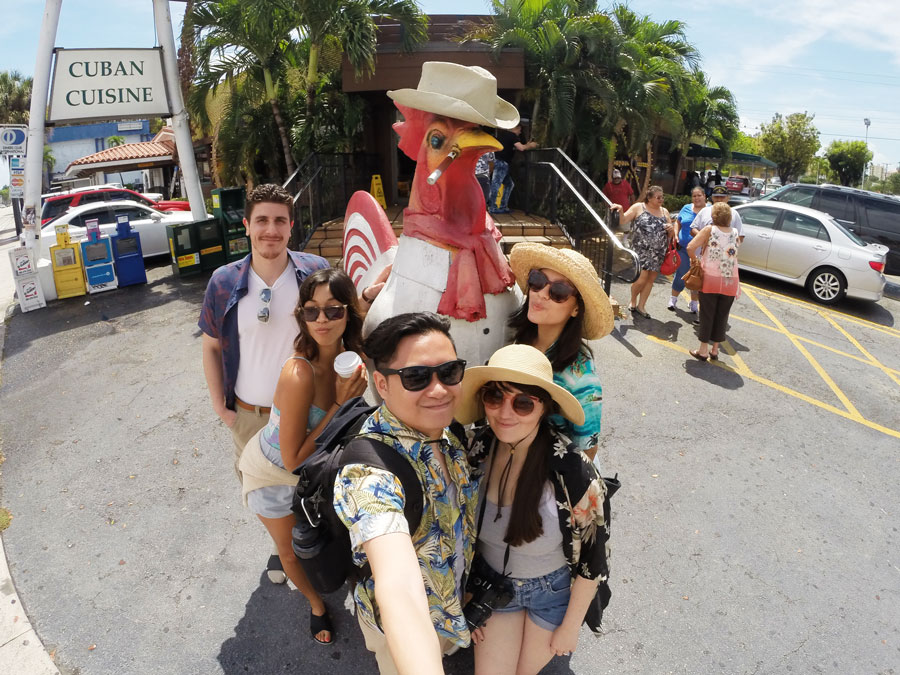 Meredith Lambert Banogon and Kevin Banogon pose with one of the roosters along Calle Ocho in front of La Carreta.