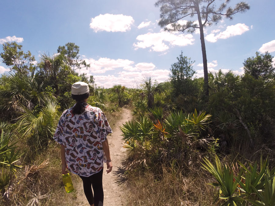 Alicia Doroteo hikes along the Gator Hook Trail in Big Cypress National Preserve on a sunny Florida day.