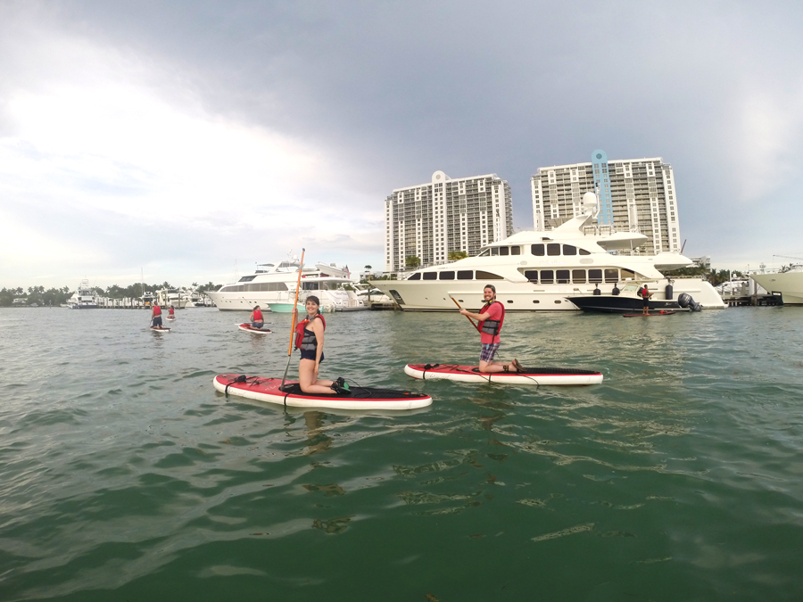 Meredith Lambert Banogon and Brennan Baxley enjoy an evening of paddle boarding in Miami, Florida.