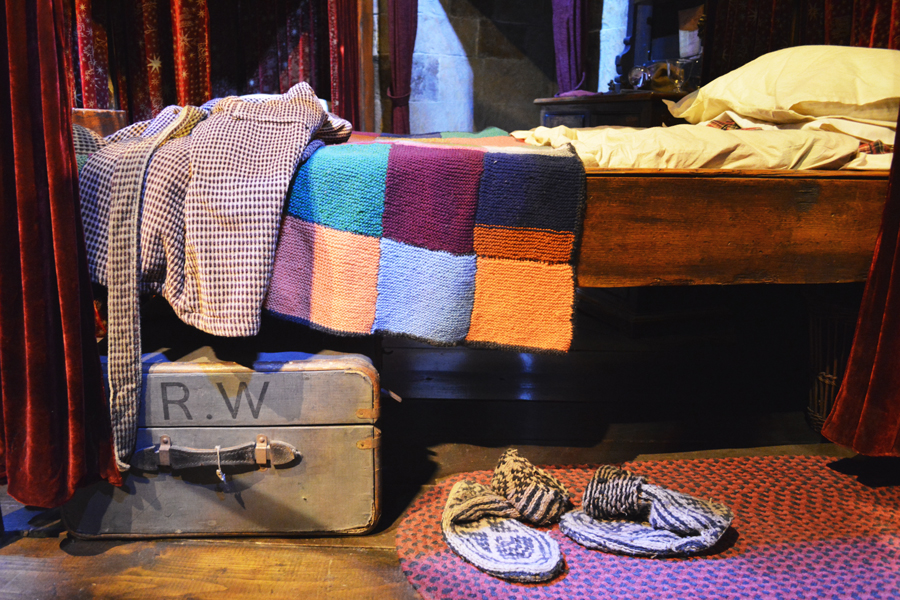 A close up of Ronald Weasley's bed in the Gryffindor boys dormitory at the Harry Potter studio tour.