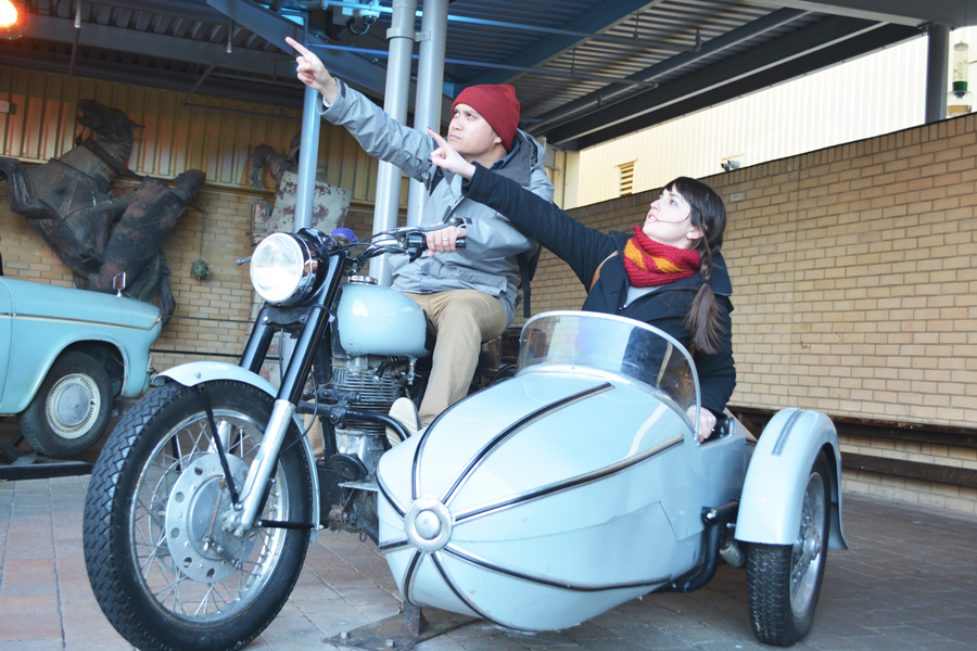 Kevin Banogon and Meredith Lambert Banogon ride a vintage motorcycle in the back lot of the Harry Potter Leavesden Studio Tour.
