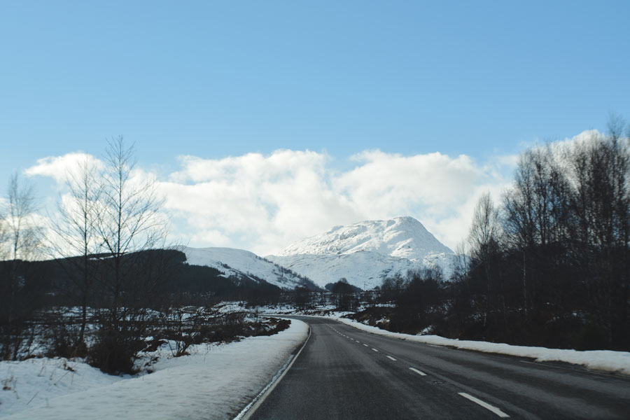 The snowy mountains along the road in Scotland make a great view during a road trip to the Isle of Skye.