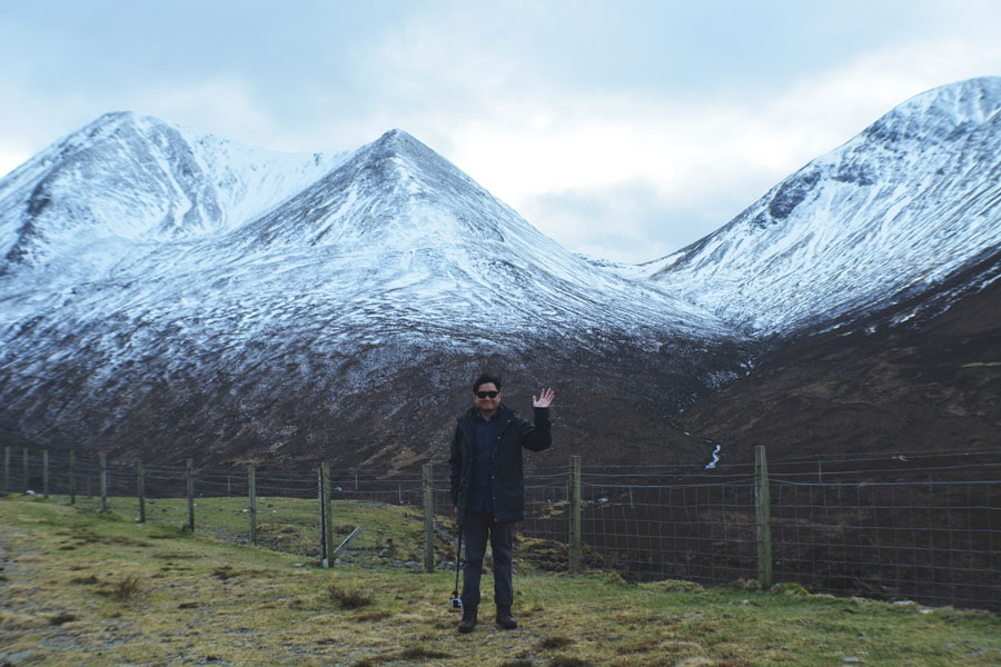 Kevin Banogon stands in front of the beautiful Scottish landscape.