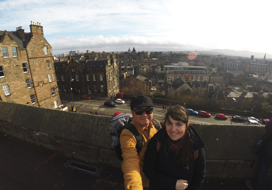 Kevin Banogon and Meredith Lambert Banogon pose together in front of the a view of Edinburgh, Scotland from the Castle.