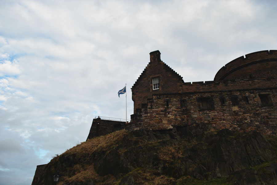 The flag of Scotland stands tall among the rocky face of the Edinburgh Castle.