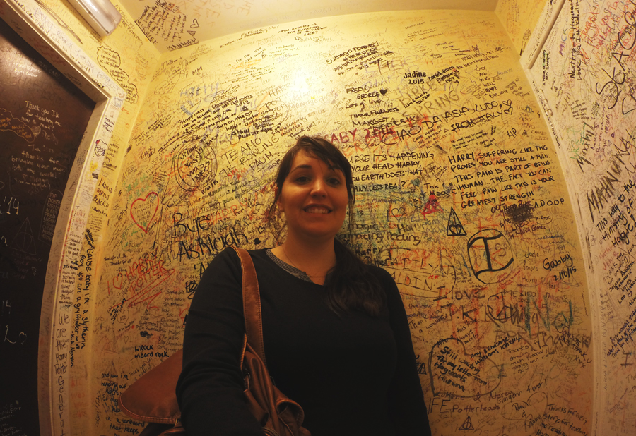 Meredith Lambert Banogon surrounded by the messages left by Harry Potter fans inside the Elephant House bathroom.