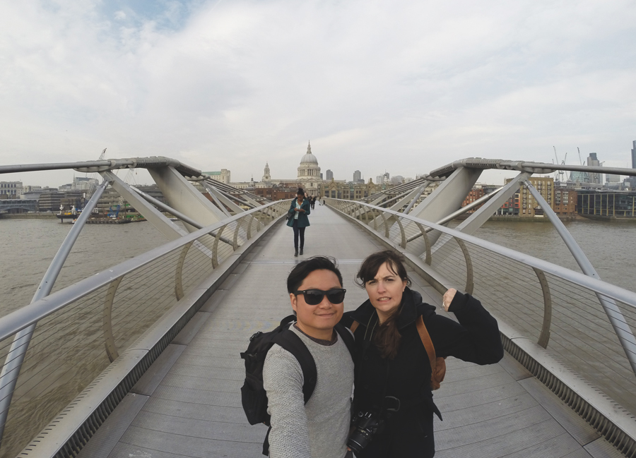 Meredith Lambert Banogon and Kevin Banogon cross the Millennium Bridge on a windy day during their London Honeymoon.