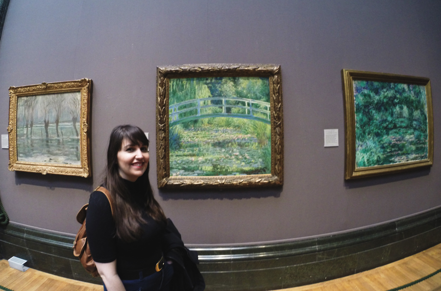 Meredith Lambert Banogon stands in front of a painting by Claude Monet.