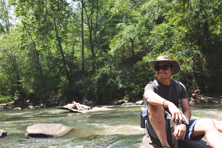 Kevin Banogon relaxes on the rocks in Vickery Creek as he watches people enjoy Old Roswell Mill Falls.