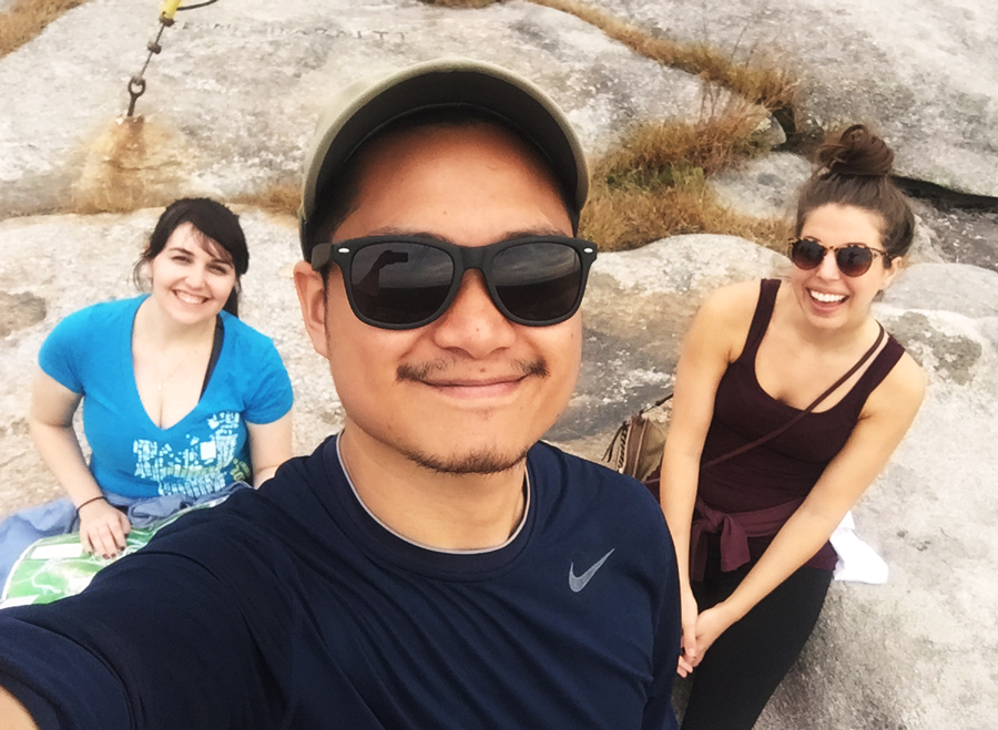 Meredith Lambert Banogon, Kevin Banogon, and Lauren Branzei rest as they reach the top of Stone Mountain.
