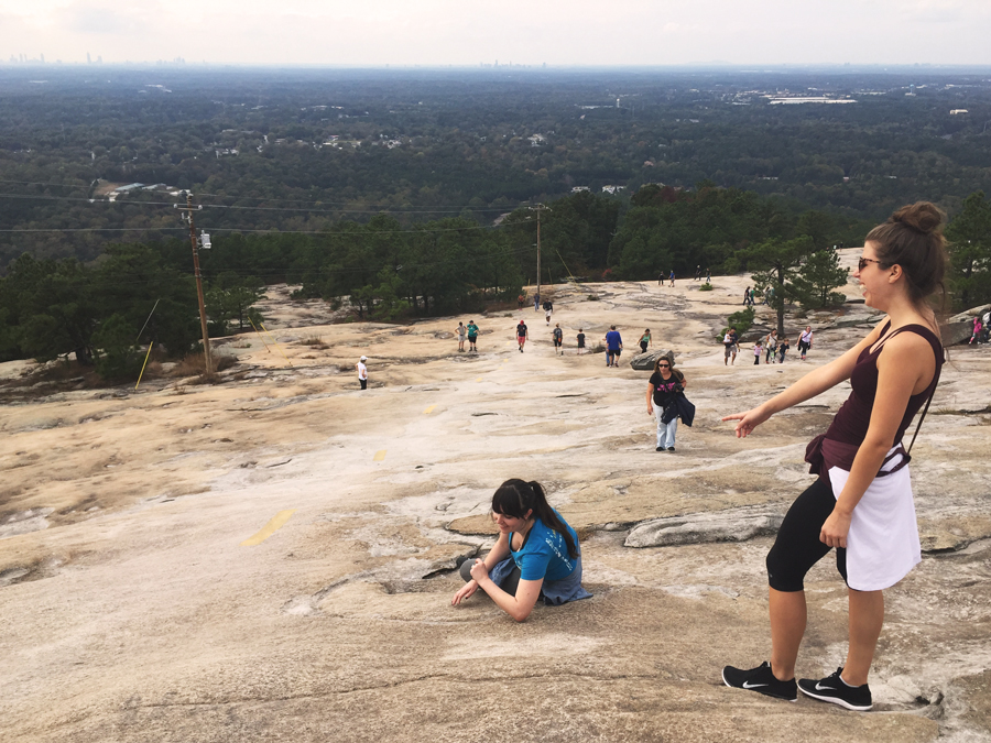 Lauren Branzei points at Meredith Lambert Banogon as she rests on the way to the top of Stone Mountain.