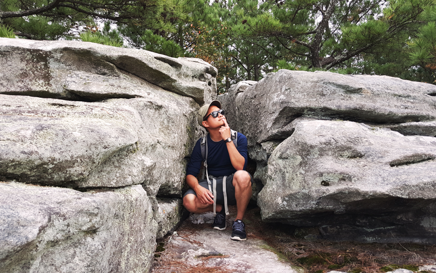 Kevin Banogon sits between two rocks at the top of Stone Mountain and contemplates the hike ahead.