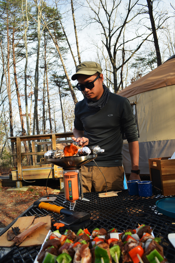 Kevin Banogon cooks pork skewers on his BioLite stove while yurt camping at Cloudland Canyon.