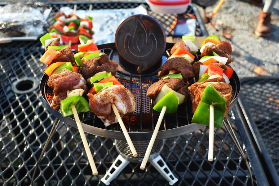 A couple enjoys pork skewers while yurt camping at Cloudland Canyon for their one year anniversary.