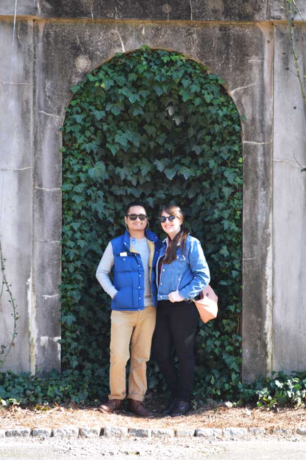 Meredith Lambert Banogon and Kevin Banogon pose in front of an ivy wall at the Swan House in Atlanta, Georgia.