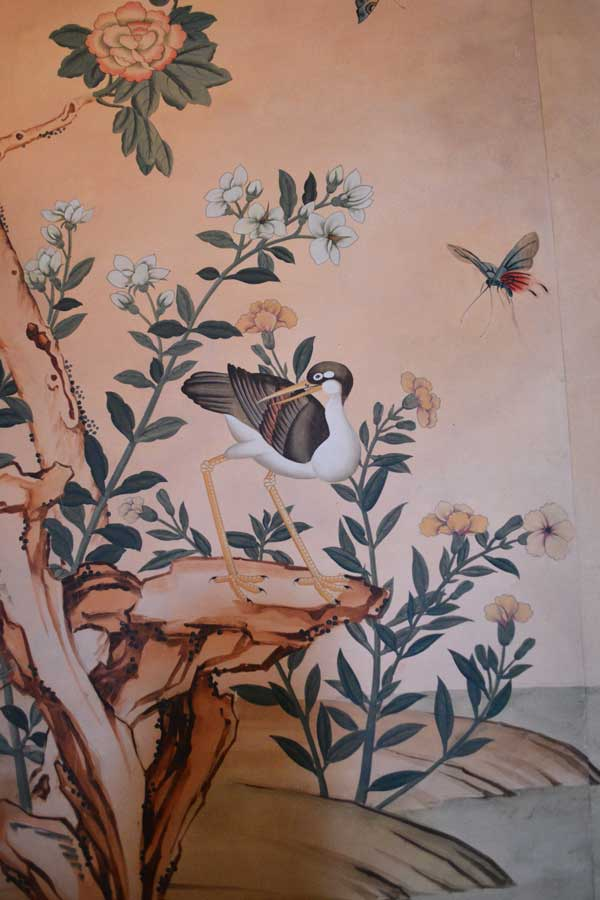 A close-up shot of the hand painted wall paper in the dining room of the Swan House features birds and flowers.