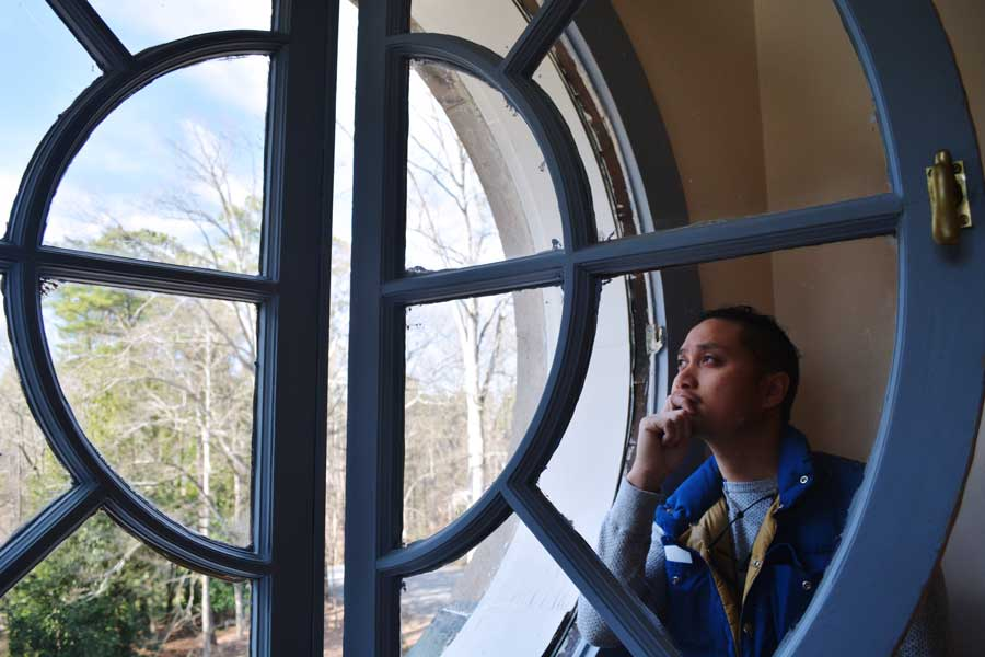 Kevin Banogon peers out of the top window of the Swan House in Atlanta, Georgia.