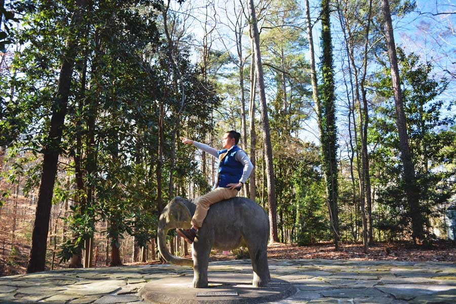 Kevin Banogon points ahead as he sits on top of an elephant statue at the Atlanta History Center.
