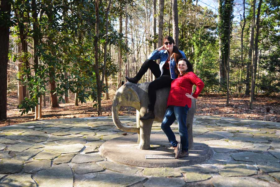 Meredith Lambert Banogon and Charlene Kirsten pose with an elephant statue at the Atlanta History Center.